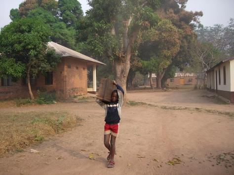 Centrafique, Sibut, 2010: un élève transporte une table de classe